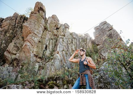 Traveling man with backpack on rock looking away