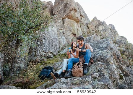 Full length portrait of a happy couple resting while hiking in mountains