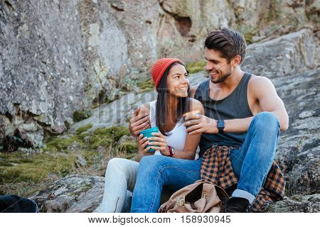 Couple sitting on rock with cups of tea. eyes to eyes