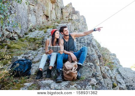 Happy smiling young couple resting with tablet computer while hiking at mountains