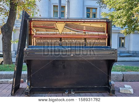 Old piano for street musicians with the front cover removed