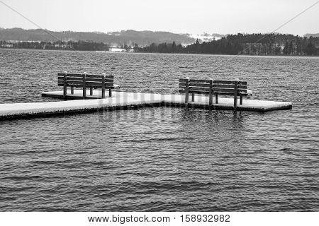 Black and white shot of two benches on a bathing jetty at winter time