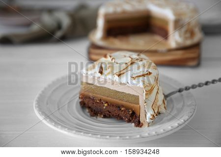 Slice of delicious cake with chocolate, nuts and pear topping on plate