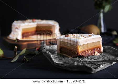 Slice of delicious cake with chocolate, nuts and pear topping on tray