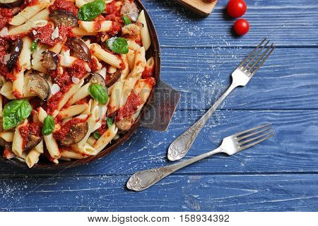 Pan with tasty macaroni and forks on wooden table