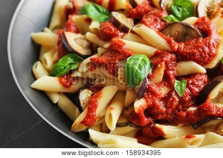 Pan with tasty macaroni, ketchup, eggplant slices and basil, close up view