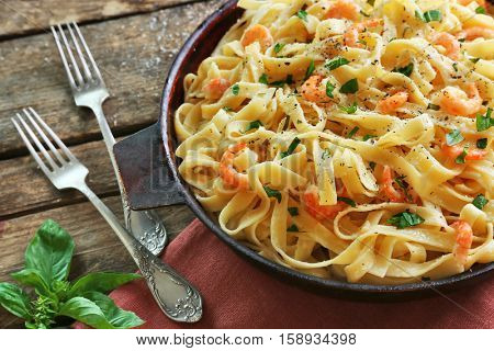 Pan with tasty alfredo pasta and forks on wooden table