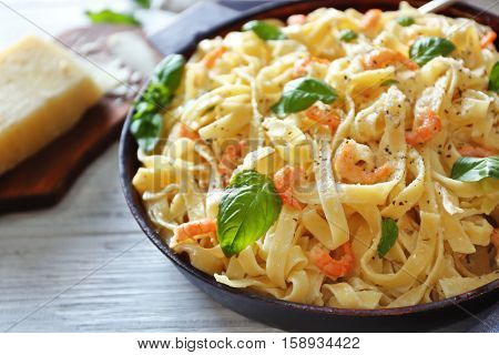 Pan with tasty alfredo pasta on wooden table