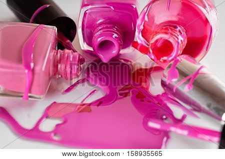 a colorful circular jars with lacquer for nails on a blue background with reflection