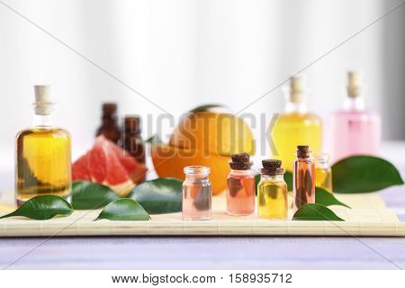 Bottles with essential oil, fruits and leaves on bamboo napkin