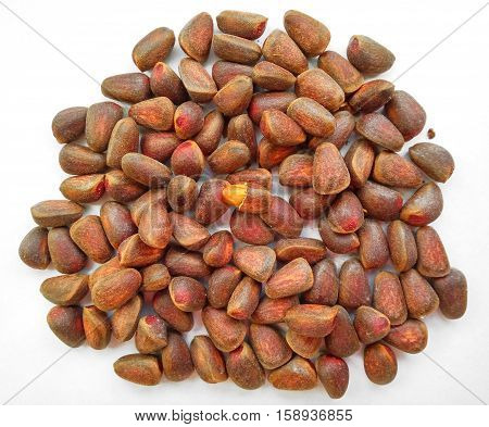 Unpeeled cedar pine nuts on white background