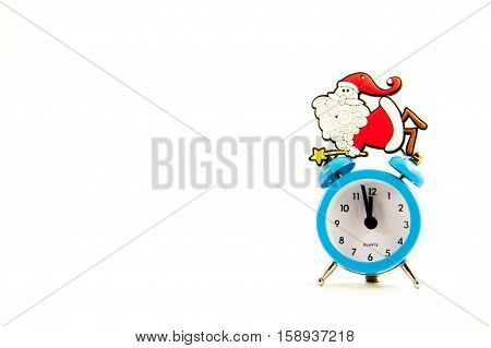Toy Santa Claus sits on the clock on a white background