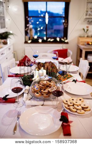 Christmas meal laid on table in decorated dining room. Roasted turkey or chicken, vegetables, cookies, Christmas wreath, glasses of red wine.