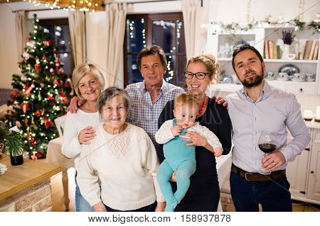 Beautiful big family celebrating Christmat together at home. Illuminated Christmas tree behind them.