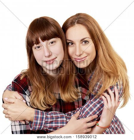 Mother and daughter. Family studio portrait over white background. Teenager girl hugs her lovely mom.
