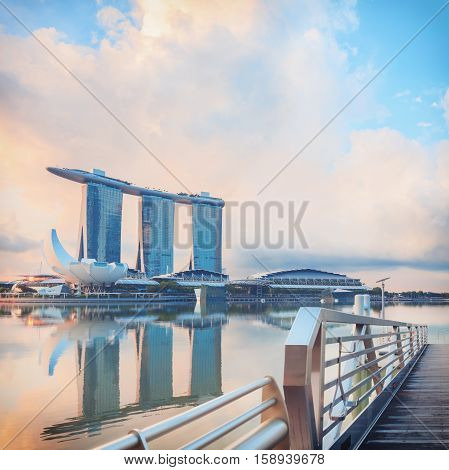 Singapore, Republic of Singapore - May 7, 2016: Marina Bay with pier on foreground. Modern city architecture at sunrise.