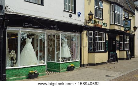 ST IVES, CAMBRIDGESHIRE, ENGLAND - JULY 20, 2016: Bridal Shop Window with dresses on show next to public house.