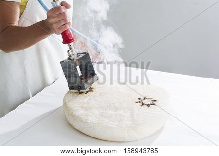 Hot marking of a fat cheese, smoke on the background