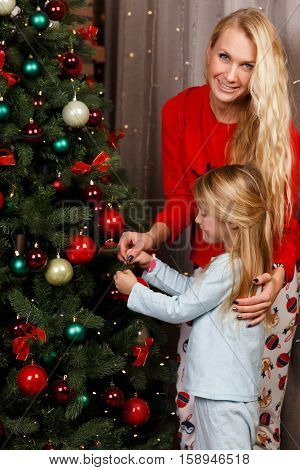 Mom and daughter in sleepwear at Christmas tree
