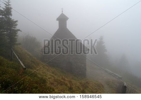 Old stone chapel built high in the mountains, is murky autumn days.