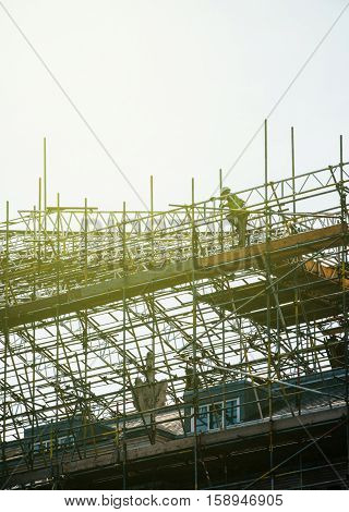Worker on complex scaffolding over an old house