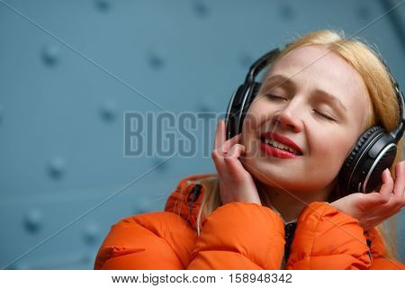 Woman with closed eyes listening music in blue wall