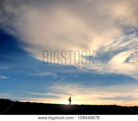 Silhouette of walking traveller at the background of magnificent clouds in blue sky and sunlight at the horizon.