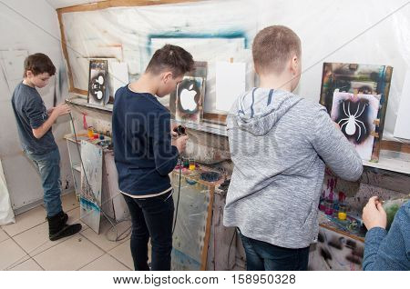 Group Of Children Teenagers Paint With An Airbrush Brightly Colored Pictures In A Artistical Studio