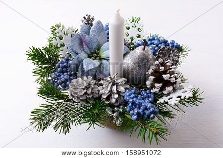 Christmas table centerpiece with candle and blue silk poinsettias. Christmas background with decorated pine cones.