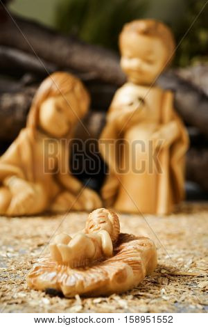 the holy family, the Child Jesus, the Virgin Mary and Saint Joseph in a rustic nativity scene, with the focus on the Child Jesus