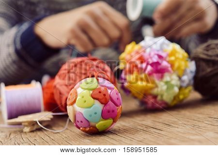 closeup of a young man making some handmade christmas ball with strings and buttons of different colors, and a pile of different haberdashery items on a rustic wooden surface