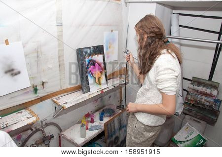 Girl Teenager Paints With An Airbrush Brightly Colored Pictures In A Artistical Studio - Russia, Mos