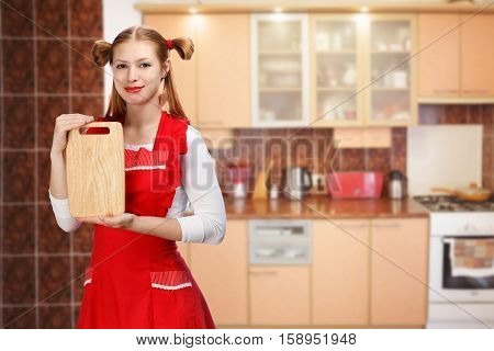 Young beautiful attractive smiling housewife in bright red apron with funny ponytails holding rectangular wooden cutting board on kitchen background.
