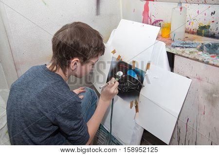 Boy Teenager Paints With An Airbrush Brightly Colored Pictures In A Artistical Studio - Russia, Mosc