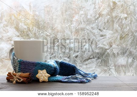 large white mug with blue scarf standing on a table with cinnamon and ginger cookies / warming drink on a winter day