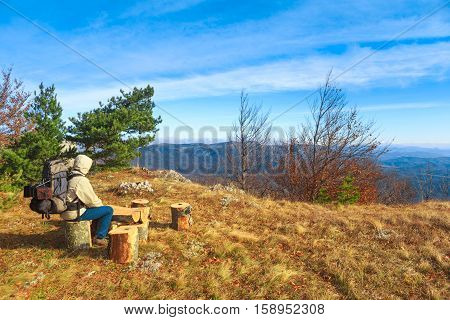 Traveller man with a backpack sits on a tree stump and admires autumnal landscape background with dry grass orange leaves blue cloudy sky and mountains at the horizon.