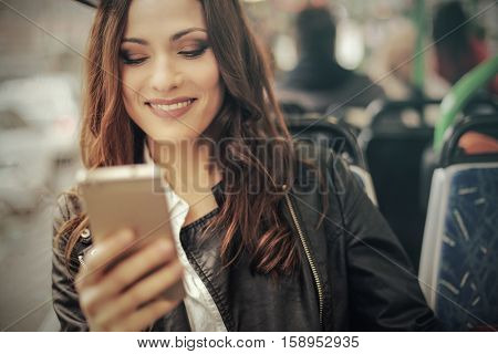 Girl on her phone while travelling on the bus