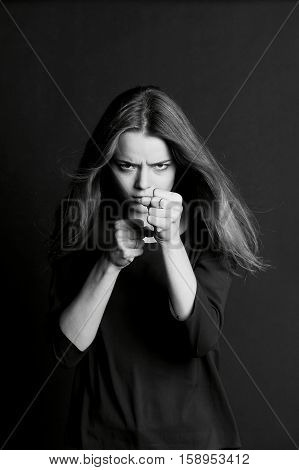 Hostile posture. Clenched fists before her face. Young beautiful girl with long hair