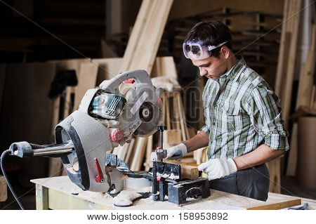 Skilled carpenter cutting a piece of wood in his woodwork workshop, using circular saw with other machinery on the background.