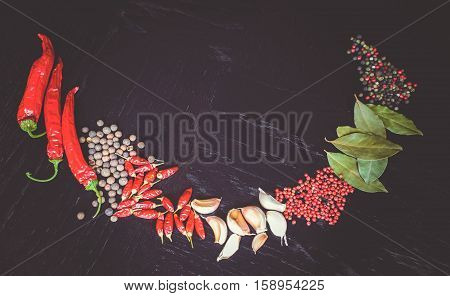 Frame of spicy background with assortment of different hot chilies, allspice, brazilian peppers, garlic and bay leaves over rusty black wooden background. Top view.