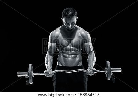 Close up of young muscular man lifting weights over dark background. Black and white color