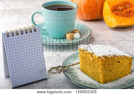 pumpkin pie, tea, pumpkin, pumpkin piece and note pad on a white wooden table