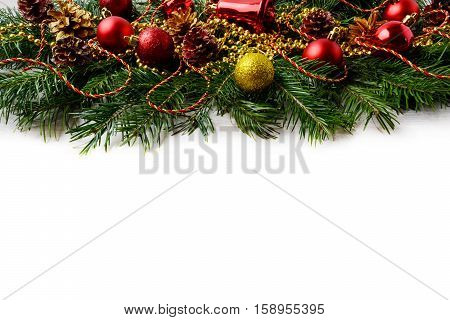 Christmas background with red ornaments and golden decorated pinecone. Christmas background with fir branches. Copy space.