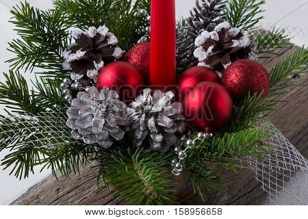 Christmas decoration with red ornaments and silver pine cones. Christmas centerpiece with silver beads.