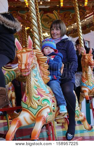 26TH NOVEMBER 2016, PORTSMOUTH DOCKYARD,ENGLAND;A mother with her young child riding on an old vintage retro carousel at the yearly Victorian Christmas festival in Portsmouth dockyard, England, 26th November 2016