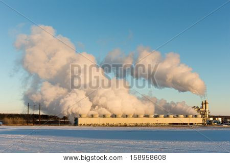 Public power plant billows steam into the clear blue winter sky as it converts natural gas to electricity. Snow on the ground. Copy space in the sky if needed.