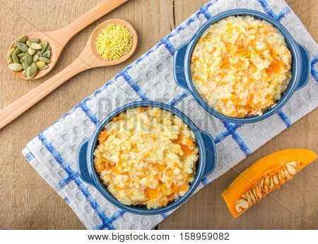 millet porridge with pumpkin in blue bowl on a kitchen towel, pumpkin seeds and millet in a wooden spoons and pumpkin on a wooden table top view