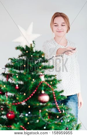 Young Girl Decorating Christmas Tree With Lights