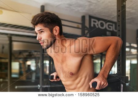 Naked model doing exercises in the gym. looking away