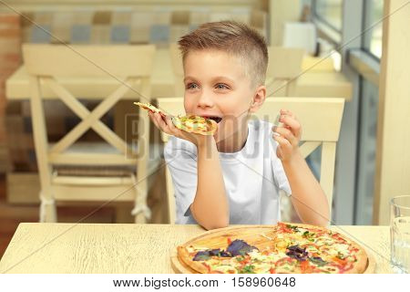 Cute boy eating pizza in restaurant